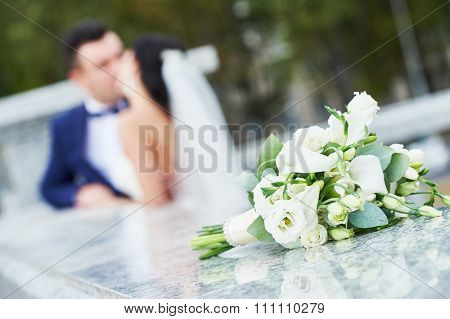 Beautiful white wedding bouquet with blurred bride and bridegroom kissing in the background - shallow dof
