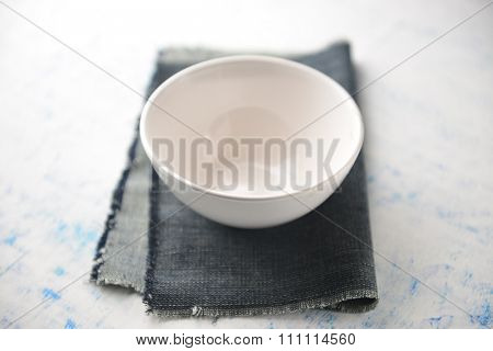 An empty white soup bowl placed on grunge napkin. Modern set up.