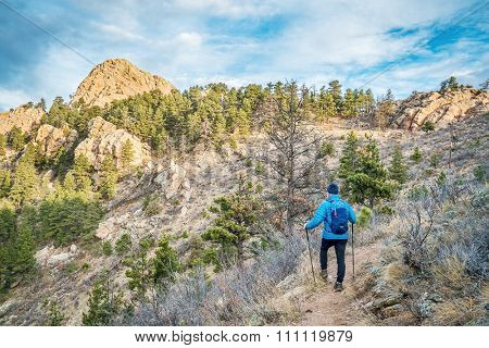 male hiker with a backpack on a trail to Horsetooth Rock, a landmark of Fort Collins, Colorado, winter scenery without snow