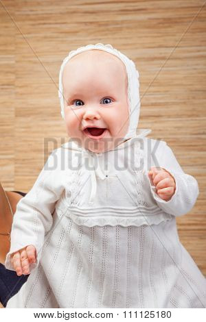 Cheerful six month baby girl wearing white christening clothes