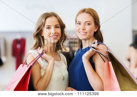sale, consumerism and people concept - happy young women with shopping bags at clothing shop
