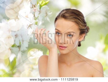 beauty, aroma, people and body care concept - young woman smelling perfume from wrist of her hand over green natural cherry blossom background