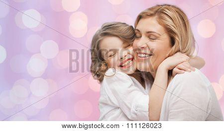 people, motherhood, family, holidays and adoption concept - happy mother and daughter hugging over holidays lights background