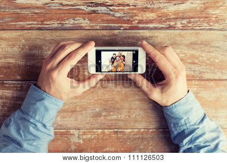 people, memory, relations and technology concept - close up of male hands holding smartphone with photo of happy friends on screen at table