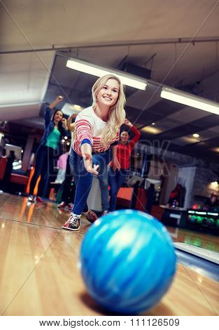 people, leisure, sport and entertainment concept - happy young woman throwing ball in bowling club