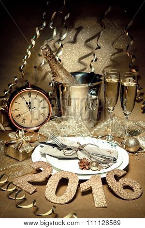 New year holiday table setting with champagne. Celebration. Place setting for new year eve. Holiday decorations. Served table