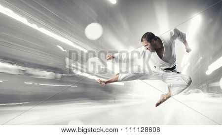 Young determined karate man jumping high in hit
