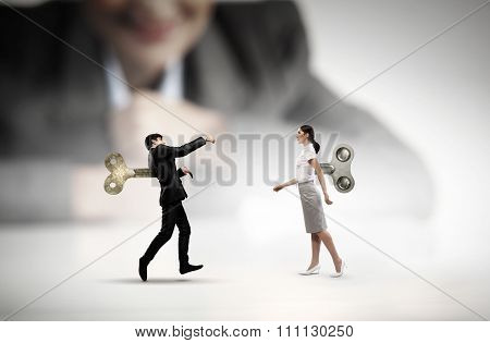 Young businessman and businesswoman walking with wind up key in his back