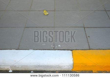 Yellow-white kerb line or curb stone border on the asphalt road.