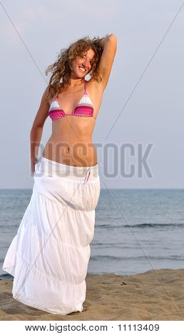 Beautiful Young Woman Near The Sea At Sunset