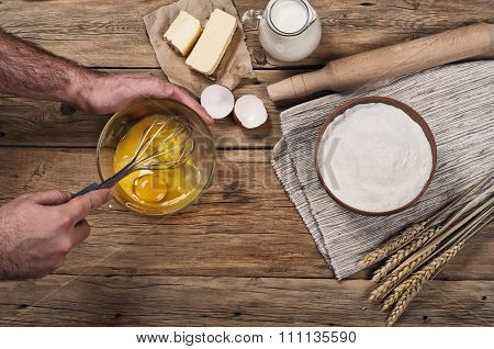 Male Chef Whipping Eggs In The Bakery On Wooden Table