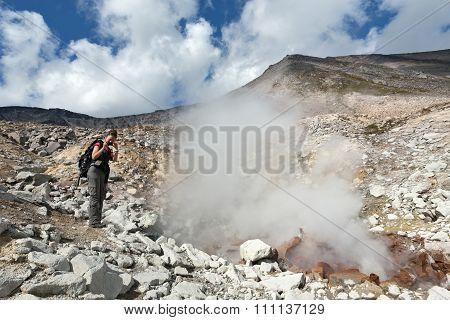Girl photographing steaming fumarole on crater active volcano. Kamchatka, Russian Far East, Eurasia