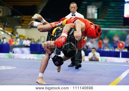 JAKARTA, INDONESIA - NOVEMBER 16, 2015: Mohsen Mohammadseifi of Iran (red) fights Van Tai Nguyen of Vietnam (black) in the men's 70kg Sanda event at the 13th World Wushu Championship 2015.