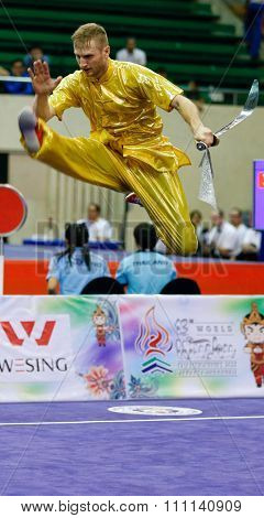 JAKARTA, INDONESIA - NOVEMBER 16, 2015: Justin Benedik of the USA performs the movements in the men's Daoshu event at the 13th World Wushu Championship 2015 at the Istora Senayan Stadium.