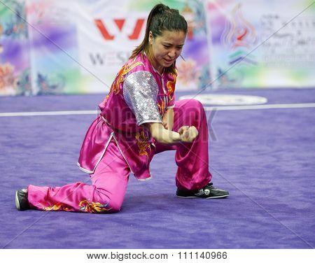 JAKARTA, INDONESIA - NOVEMBER 16, 2015: Elizabeth Lim of Australia performs her movements in the Women's Compulsory Nanquan event at the 13th World Wushu Championship 2015 in Istora Senayan Stadium.