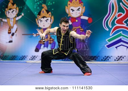 JAKARTA, INDONESIA - NOVEMBER 16, 2015: Mario Martinez of Spain performs the movements in the men's Nandao event at the 13th World Wushu Championship 2015 at the Istora Senayan Stadium.