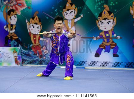 JAKARTA, INDONESIA - NOVEMBER 16, 2015: Wai Keong Chio of Macao performs the movements in the Men's Nandao event at the 13th World Wushu Championship 2015 at the Istora Senayan Stadium, Jakarta.
