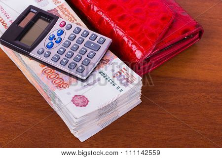 A bundle of money, red leather wallet and calculator are on the table