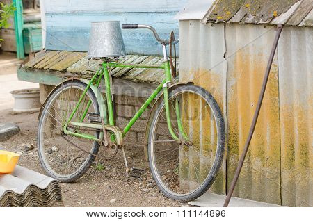 Old Bicycle With A Bucket On The Saddle