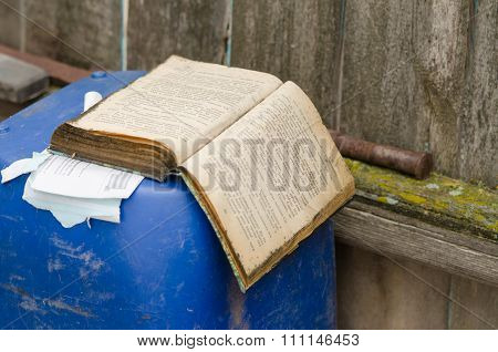 An Old Book Lies In The Barrel Of The Fence