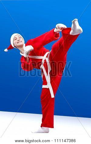 Sportswoman dressed as Santa Claus hits a kick leg