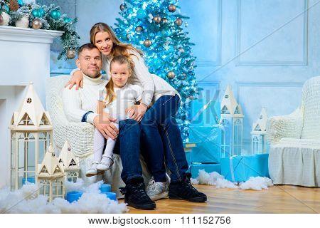 Happy family standing near Christmas tree