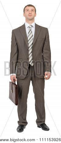 Businessman with suitcase looking up