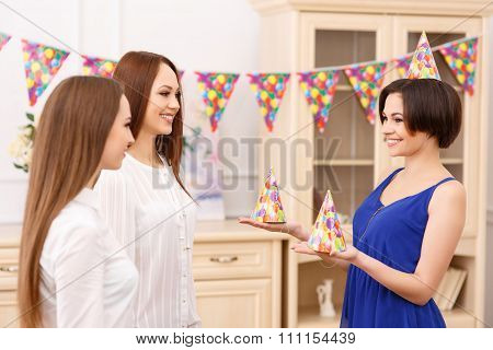 Young girl offering party hats for her friends.