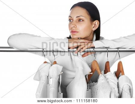 Portrait of young female with selection of winter clothes. Space for text. Sale season concept.