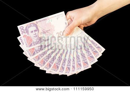 Ukrainian money fanned out in her hand isolated on black backgro