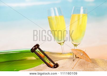 Champagne bottle and glasses with hourglass in sand