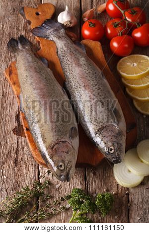 Raw Rainbow Trout With Ingredients On Board Close-up. Vertical Top View