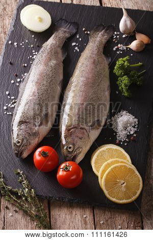 Two Raw Rainbow Trout With Ingredients On A Slate Board. Vertical