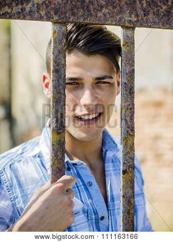 Handsome young man behind metal cage bars
