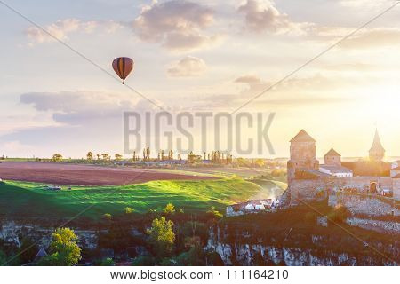 View on the castle in Kamianets Podilskyi and air balloon during sunset