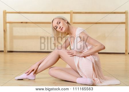 Professional ballet dancer is stretching on the floor.
