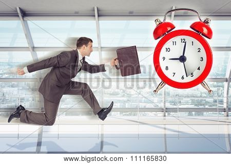 Businessman running with alarm clock background
