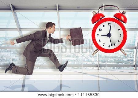 Businessman running with alarm clock background