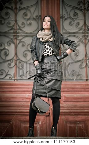 Attractive young woman in winter fashion shot with wrought iron decorated doors in background