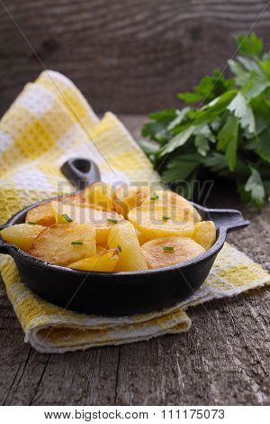 New Potatoes Fried In A Cast Iron Skillet Over An Old Wooden Background