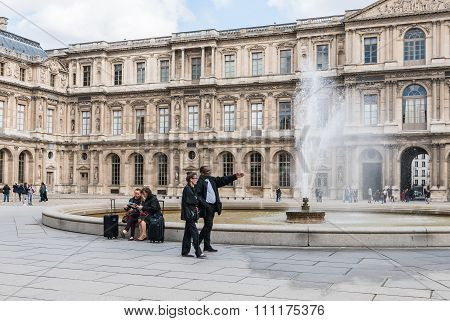 Museum Workers And Tourists Near Fountain At
