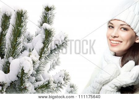 attractive young caucasian woman in warm clothing  in studio isolated on white smiling christmas tree covered with snow