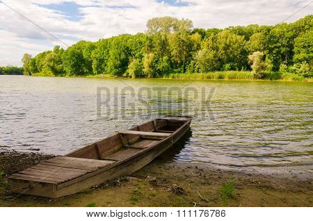 Summer landscape - forest and chained wooden boat at the lake