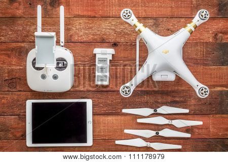 Fort Collins, CO, USA - August 31, 2015:  DJI Phantom 3 quadcopter drone with a set of propellers, radio controller, spare battery and iPad - top view  against rustic wooden  table.