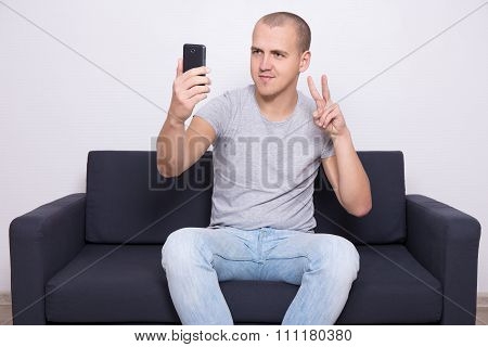 Young Man Sitting On Sofa And Taking Selfie Photo With Mobile Phone