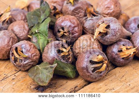 Healthy ripe Medlars on the old wooden table