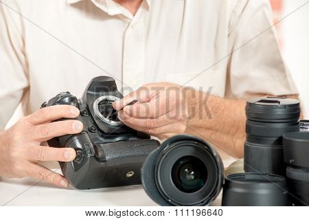 Close Up Of Photographer Hand Cleaning Sensor Of His Camera