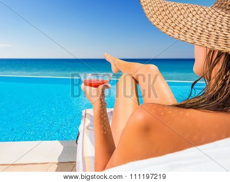 Beautiful woman with a hat is relaxing in an infinity pool with a breathtaking view