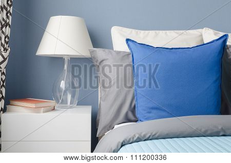 Blue Pillow On Bed With Glass Lamp On White Table In Modern Blue Bedroom