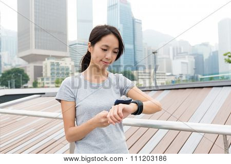 Asian Young Woman sync the data with her watch and mobile phone